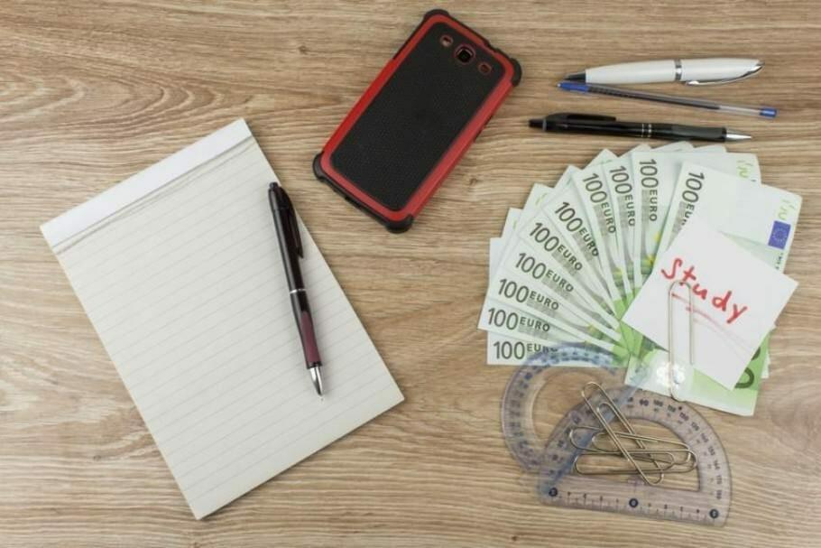 Schreibblock, Smartphone, Geometrie-Werkzeug und Geldscheine auf einem Holztisch