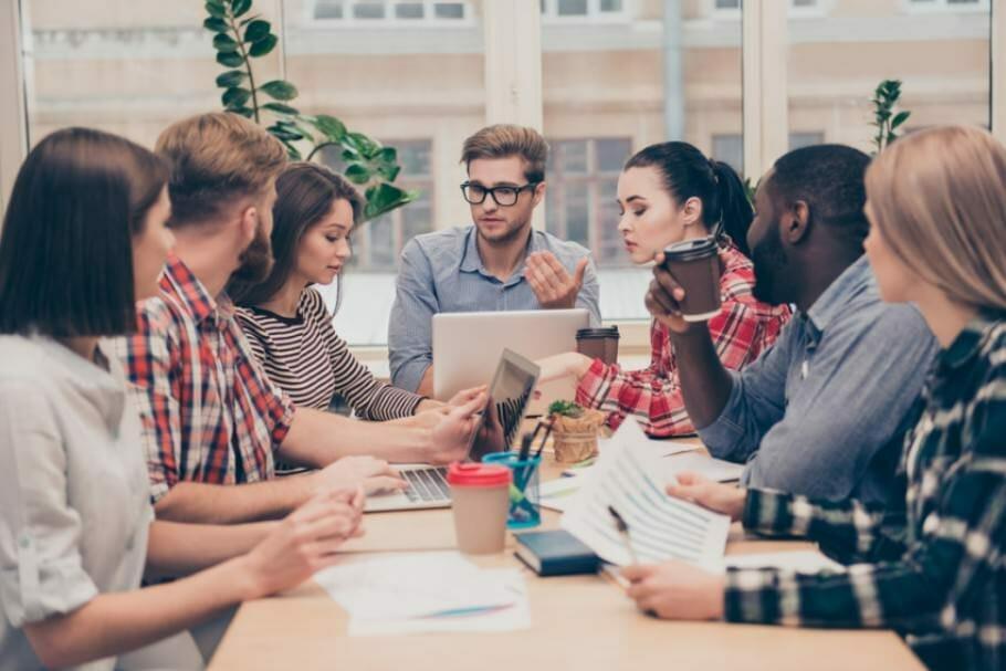 Sieben junge Menschen sitzen mit Laptop, Papieren und Stiften bei einem Meeting zusammen um einem Tisch